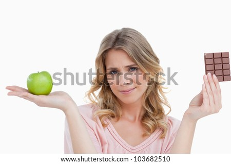 Young woman looking at the camera while holding an apple and a chocolate bar
