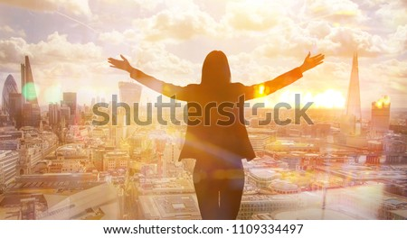Young woman looking at the City of London, financial district. Early morning. Sun rise. Future, planning and business progress concept. #1109334497