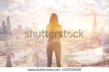 Young woman looking at the City of London, financial district. Early morning. Sun rise. Future, planning and business progress concept. #1109334500