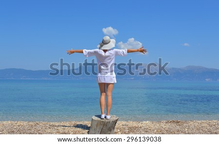 Young woman looking at the mountains above sea with her arms wide open on a sunny summer day