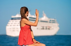 Young woman looking at the ship and waving her hand, view from the back