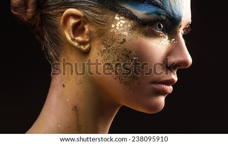 Young woman looking at the side with fantasy make up. Ususual face art studio shot. Copyspace. High resolution