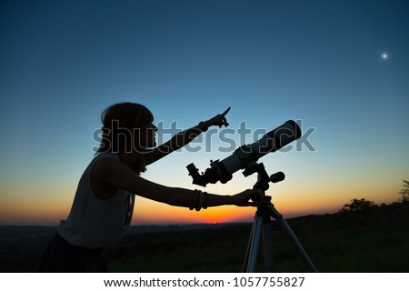 Young woman looking at the sky with a astronomical telescope.