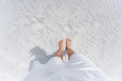Young woman looking down pov point of view perspective on bare feet standing in white sand in Fort Walton Beach, Florida, in white dress, flat top view with shadow