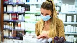 Young woman looking for a product in a store wearing a mask due to coronavirus
