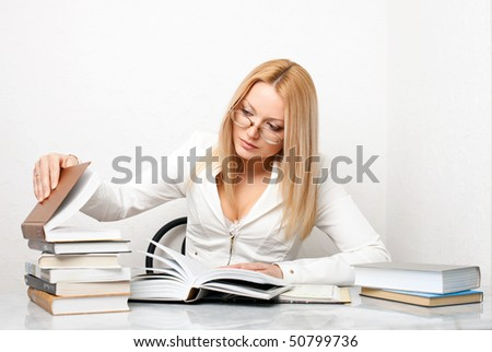 Young woman looking for some information in books, educational concept