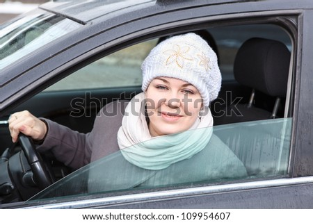 Young woman looking from window in car and smiling