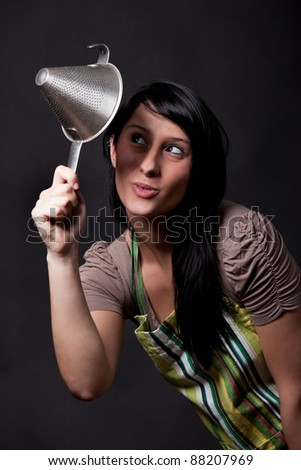 young woman looking in a sieve