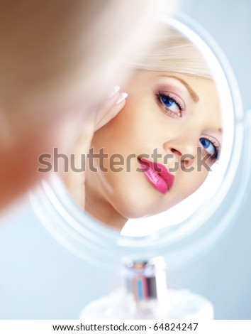 Young woman looking in cosmetic mirror