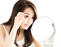 young woman looking into mirror and checking eyes