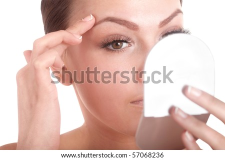 Young woman looking into mirror. Isolated.