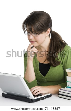 young woman looking like a student/teacher, with laptop, stack of books,green apple