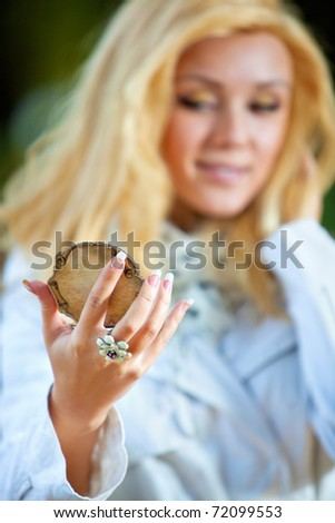 Young woman looking on mirror. Focus on hand.