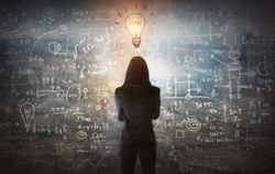 Young woman looking on the black board with mathematical formulas and calculations. Bright idea, way of thinking, discovery and challenge concept.