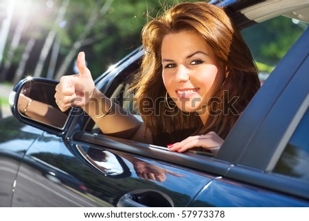 Young woman looking out of car and showing success handsign.