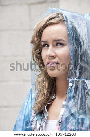Young woman looking pensively up at the sky waiting for the rain