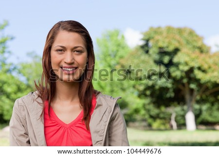 Young woman looking straight ahead while smiling in a bright grassland area