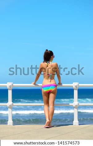 Young woman looking the blue sea on summer bright day. Sexy girl in colorful bikini watching the coastline on beach vacation. Copy space.