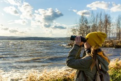 Young woman looking through binoculars at birds on the lake. Birdwatching, zoology, ecology. Research, observation of animals. Ornithology