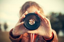 Young woman looking through camera lens
