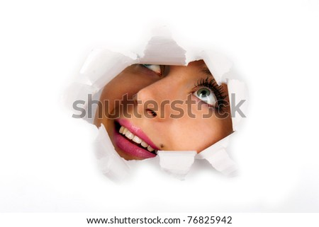 Young woman looking through hole in a paper