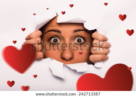 Young woman looking through paper rip against hearts
