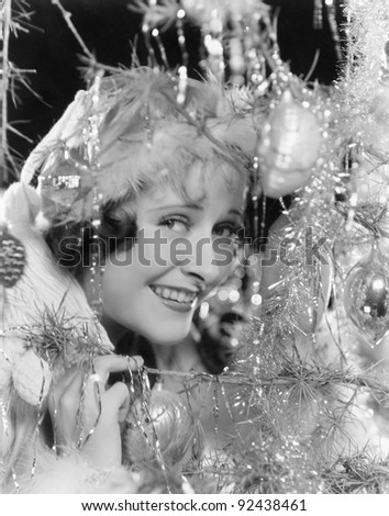 Young woman looking through the branches of a Christmas tree with ornaments
