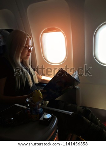 Young woman looking through window in airplane #1141456358