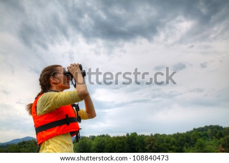 Young woman looking to sky through binoculars
