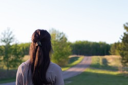 Young woman looking up the road ahead of her at sunset