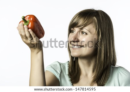 Young woman looks at a red pepper, isolated on white background