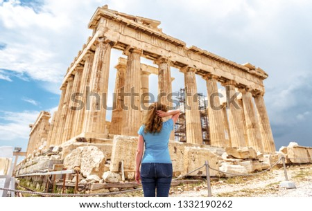 Young woman looks at Ancient Greek Parthenon on the Acropolis of Athens, Greece. This place is a top tourist attraction of Athens. Adult girl traveler visits Athens. Traveling and vacation in Athens.
