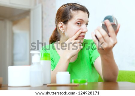 Young woman looks on her face in mirror at home