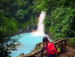 Young woman looks out over a picturesque rain forest waterfall in Costa Rica.