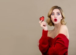 Young woman looks surprised to the camera and holds a red heart in her hands. Model with perfect young skin and professional makeup with red lips poses with red heart.  Christmas and New Year concept.