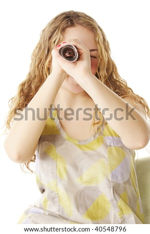 Young woman looks through scrolled paper against white background