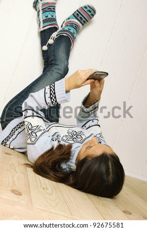 Young woman lying at home on the floor, legs raised up and lean on the wall with a mobile phone