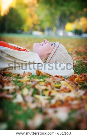 Young woman lying down in the fall leaves