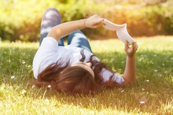 young woman lying down on grass reading a book