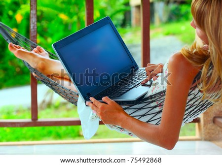 Young woman lying in a hammock and looking to a laptop