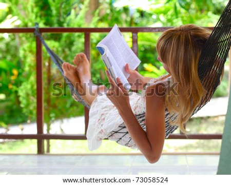 Young woman lying in a hammock and reading a book