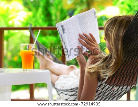 Young woman lying in a hammock in green garden and reading a book
