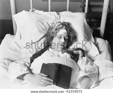 Young woman lying in bed, sleeping and holding a book