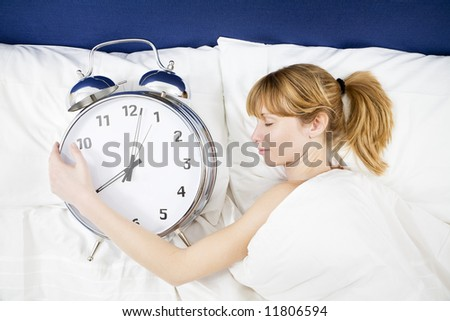 Young woman lying in bed with eyes closed, holding a huge alarm clock