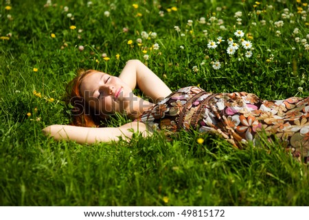 Young woman lying in grass dreaming summer day