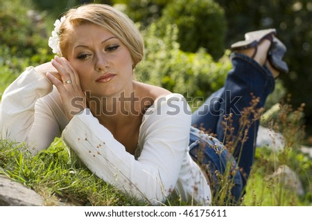 Young woman lying in the grass on a hot spring day, day dreaming about something.