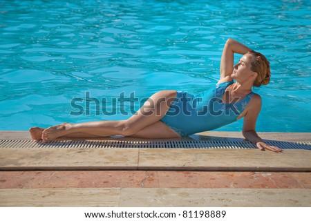 Young woman lying near the swimming pool the sun beams