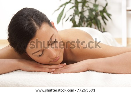 young woman lying on a massage table. relaxing with eyes closed