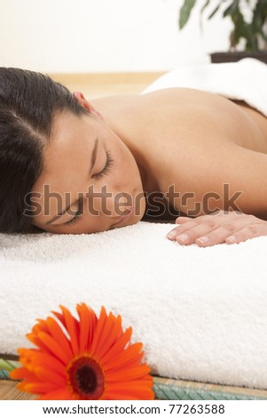 young woman lying on a massage table with flower. relaxing with eyes closed