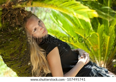 Young woman lying on a palm tree on a tropical resort